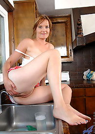 Sadie sits on the edge of the kitchen sink and washes her mature pink pussy